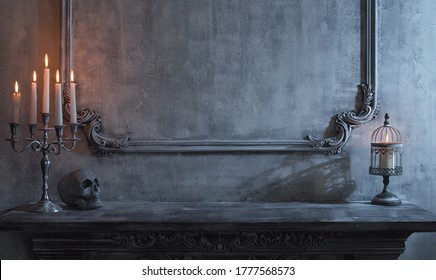 Mystical Halloween still-life background. Skull, candlestick with candles, old fireplace. Horror and witchery.