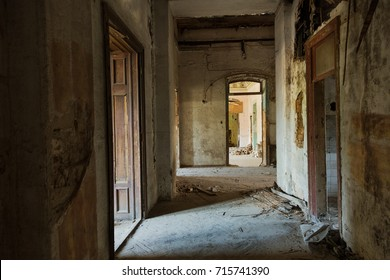Mystical interior, ruins of an abandoned ruined building of an ancient 18th century building. Old ruined walls, corridor with garbage and mud. Destroyed molding, gypsum decorations, bas-relief