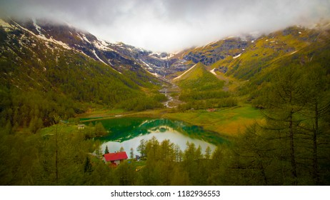 Mystical and marvelous view of the lake in Alps valley between mountains and green trees. Holliday home with reed roof beside the lake and crystal clear river stream from top of mountains