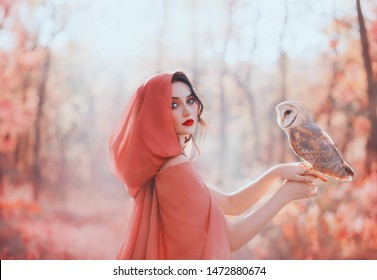 mystical pagan woman with covered head in peach scarf in forest, holds barn ow