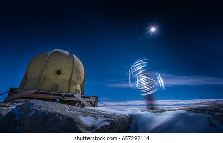 Mystical Person spinning light outside of dome building in moonlight