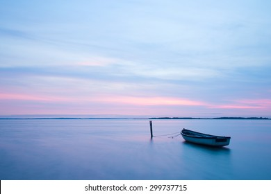 Mystical sea. Abstract natural backgrounds. Moon scene after sunset with still water and vintage boat.