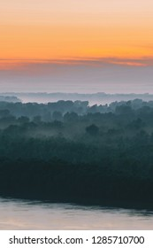 Mystical view on riverbank of large island with forest under haze at early morning. Mist among layers from tree silhouettes under warm predawn sky. Morning atmospheric landscape of majestic nature.