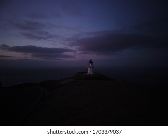 Mystical view towards lighthouse after sunset with purple sky and dark clouds in Cape Reinga, New Zealand