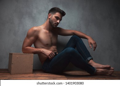 Mystified young guy looking to the side and resting his arm on his knee while leaning on a box and sitting on gray studio background