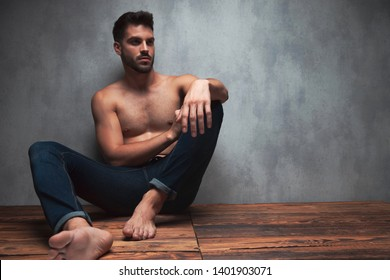 Mystified young man looking sideways and resting his arm on his knee while wearing only jeans, sitting and leaning on gray studio background