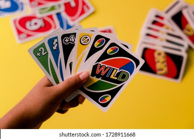 Mysuru, India - May 04, 2020: Uno cards held against a deck of cards on a yellow background with copy space. Enjoying family time during lockdown