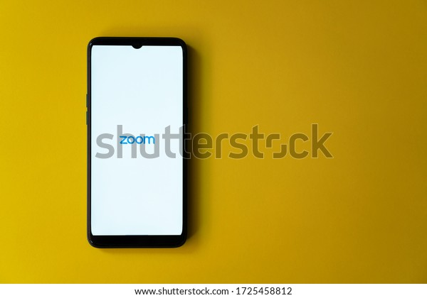 Mysuru, India - May 04, 2020: Zoom app home page on a smart phone against yellow extendable background with copy space