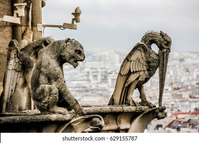 Mythical creature gargoyle on the roof of Cathedral Notre Dame de Paris. View from the tower.
