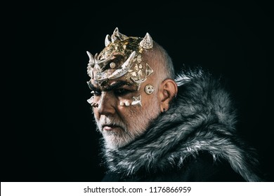 Mythical king of permafrost realm in fur collar isolated on black background. Magical beast with golden reptile skin and sharp thorns on face, fantasy and fairy tale concept.