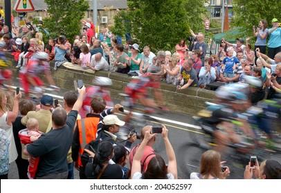 MYTHOLMROYD, UNITED KINGDOM - JULY 6, 2014: Crowd of  spectators watch the Tour de France peleton riding through Mytholmrod, Halifax, UK.