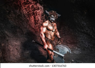 mythological minotaur  half bull half man stands in a rock cave in an aggressive stance. A monster of ancient Greek myth angry with axe in cave.