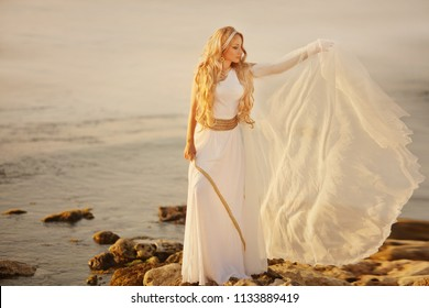 Mythology, Greek goddess, blond woman with silver laurel wreath dressed in white silks in the wind. sunset in ancient greece– stock image