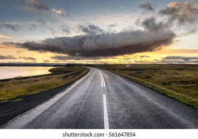 Myvatn, Iceland - Single dramatic cloud hovers above an empty road leading into sunset on the horizon