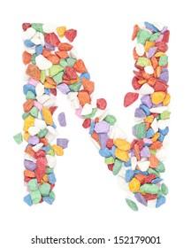N alphabet colorful gravel on white background.