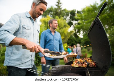 n a summer evening,  two men  in their forties prepares a barbecue for  friends gathered around a table in the garden