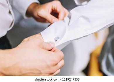 Mężczyzna zapiął białą koszulę. Na mankietach znajduje się jasny klips. Formalny dress code. - Shutterstock ID 1119247358