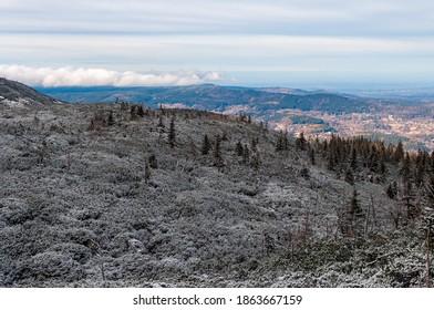 Na pierwszym planie w cieniu ośnieżone krzewy i drzewa na wzgórzu. Dale w słońcu dolina z miasteczkiem i wzgórze pokryte chmurami. Niebieskie niebo.   - Shutterstock ID 1863667159