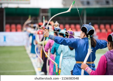 Naadam festival Mongolia archery, Mongolian women in traditional Mongolian dress shooting arrows with Mongol bow and arrow, colorful traditional costumes during Naadam competition in july