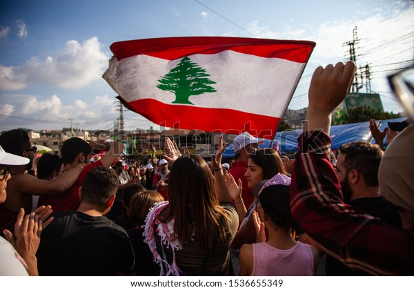 Nabatieh, South Government / Lebanon - 10 20 2019: Lebanese Protesters rising Lebanon Flag in the Sky at the Revolution against the Government