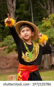 NABAWAN, SABAH, MALAYSIA - OCTOBER 11 2016 : Stylish cute boy with traditional Murut clothes in performing Semurba Tari dance.