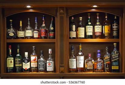 Naberezhnye Chelny, Tatarstan / Russia  September 21, 2016: Bottles of various alcoholic drinks at wooden Bar cabinet