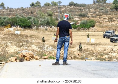 NABI SALEH, PALESTINE - AUGUST 8, 2014: A masked Palestinian holds a stone as he stares down Israeli soldiers during clashes in Nabi Saleh, Palestine on August 8, 2014.