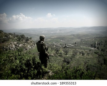 NABLUS, ISRAELI OCCUPIED TERRITORIES IN THE WEST BANK - 24, APRIL, 2007: An Israeli soldier with the Israeli Defense Forces overlooks the hills around Nablus while being on patrol.