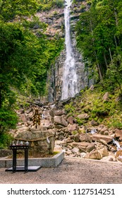 Nachi no Taki waterfall, whose name is written in Japanese on the wooden placard in front of the fall, in a blur background of trees on the cliff in Shingu, Japan viewed on April 27 2018