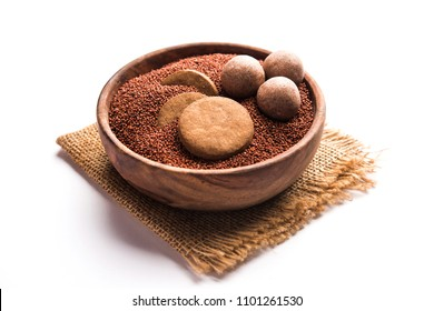 Nachni / Ragi laddu and biscuits or cookies made using  finger millet, sugar and ghee. It's a healthy food from India. Served in a bowl or plate with raw whole and powder. Selective focus