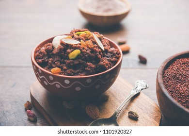 Nachni or Ragi puttu or Halwa or Sheera made using  finger millet, garnished with dry fruits. It's a healthy food from India. Served in a bowl with raw cereal with powder