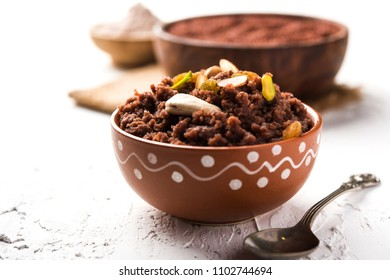 Nachni or Ragi puttu or Halwa or Sheera made using  finger millet, garnished with dry fruits. It's a healthy food from India. Served in a bowl over moody background. Selective focus