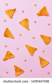 Nacho chips and corn beans arranged in a pattern on a pink background