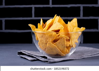 Nacho chips in the glass bowl against the black brick wall. Low key photo. Mexican cuisine snack