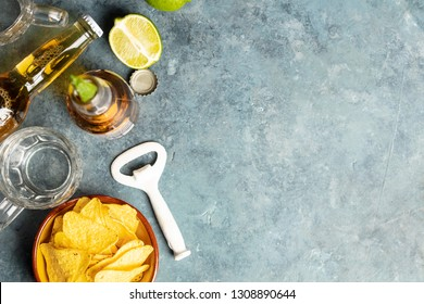 Nachos and beer on blue background, flat lay