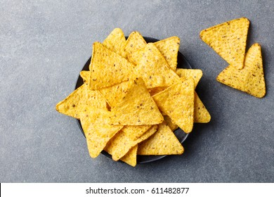 Nachos chips in bowl. Grey stone background. Top view.