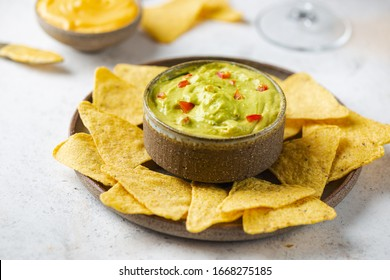 Nachos chips in a bowl with sauces guacamole and beer over white stone background.