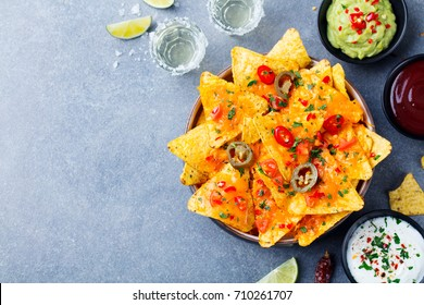 Nachos chips with melted cheese and dips variety. Top view. Copy space.