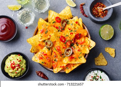 Nachos chips with melted cheese and dips variety in black bowl. Top view.