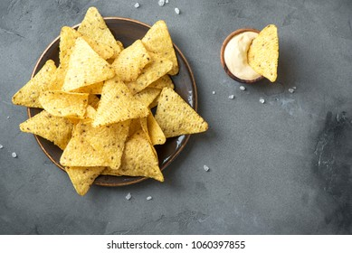 Nachos chips and melted cheese. Tortilla corn mexican nachos chips in bowl and cheese sauce dip on grey stone background, copy space.