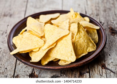 Nachos chips on brown ceramic plate. Rustic wooden background.