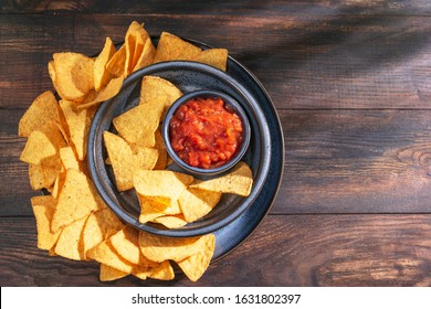 Nachos corn chips on blue plate with salsa dip sauce on a wooden rustic table, top view, flat lay, copy space. Beer crispy snack, traditional Mexican food. Sunny light with shadows.