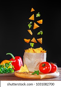 Nachos dynamically fly in the package. Tomatoes and pepper. The concept of food and delicious snacks.