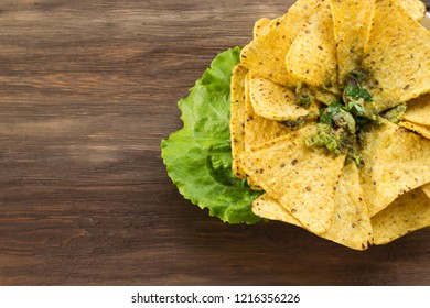 Nachos Guacamole with salad leaf in plate on the wooden background. Recipe, cooking, menu concept. Copy space, flat lay, top view, layout design