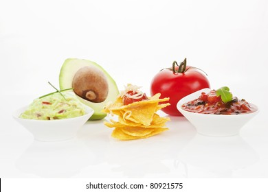 Nachos with guacamole and tomato dip and fresh avocado and tomato isolated on white background.