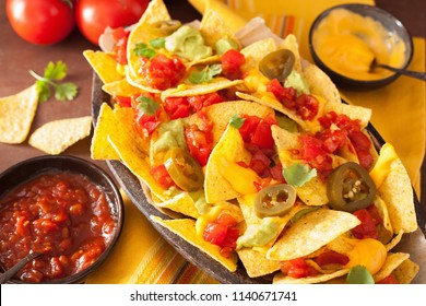 nachos loaded with salsa, cheese, guacamole and jalapeno