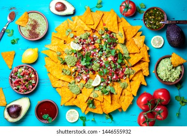 Nachos. Mexican food concept. Yellow corn totopos chips with different sauces salsas - pico del gallo, guacamole, salsa verde, chili pebre and on blue gray background, top view