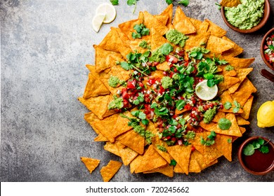 Nachos. Mexican food concept. Yellow corn totopos chips with different sauces salsas - pico del gallo, guacamole, salsa verde, chili pebre and on stone gray background, top view