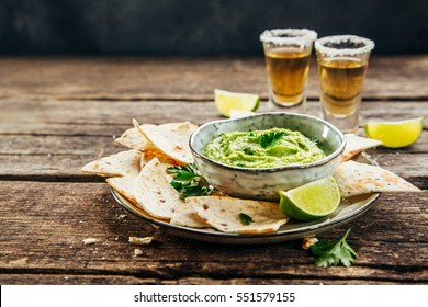 Nachos on plate and avocado sauce and tequila shots with lime for drinking