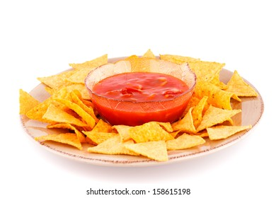 Nachos on plate and red sauce isolated on white background.
